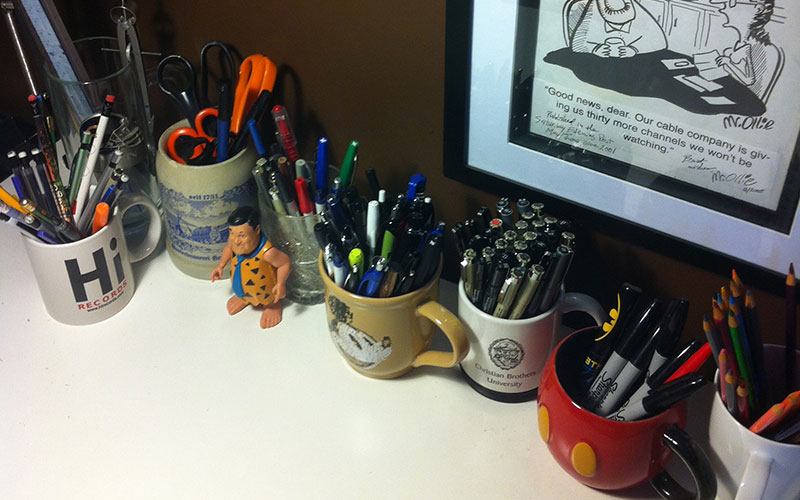 Various pens/pencils in random cups